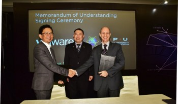 Dr. Karl Ng Hou, Ir.,  looks on as, Laurence Si, shakes hands with Dr. Andy Seddon after the signing ceremony
